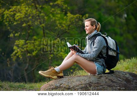 Woman backpacker writing notes hiking in summer forest and stopped to have rest. Travel hiking backpacking tourism and people concept