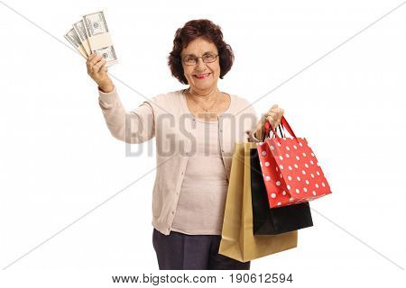 Mature woman with bundles of money and shopping bags isolated on white background