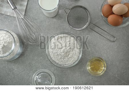 Bowl with flour, sieve and ingredients for dough on light background, top view