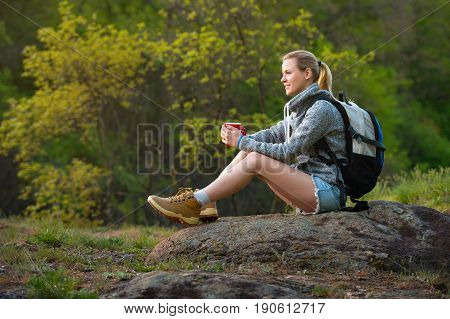 Woman backpacker hiking in summer forest and stopped to have rest with cup of tea. Travel hiking backpacking tourism and people concept