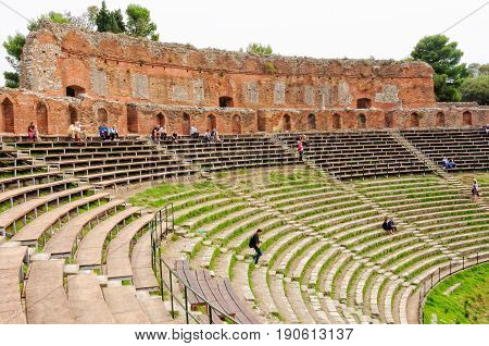 Tourists sit on the grandstand and admire the remnants of the ancient Greek theater - Taormina, Sicily, Italy, 22 October 2011