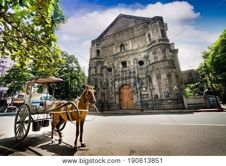 Horse Drawn Carriage parking in front of Malate church , this historical church is located in Intramuros the oldest district and historic core of  Manila Philippines