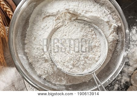 Sieve and bowl with flour on table, close up