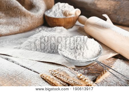 Sieve with flour on wooden background