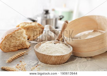 Bowl with flour, sieve and bread chunk on blurred background