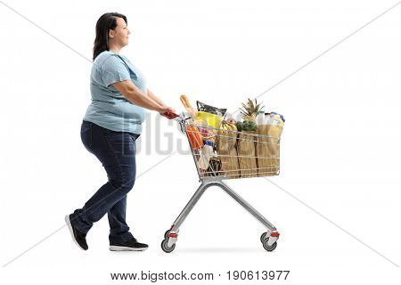 Full length profile shot of a woman pushing a shopping cart filled with groceries isolated on white background