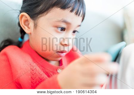 Little girl looking at mobile phone