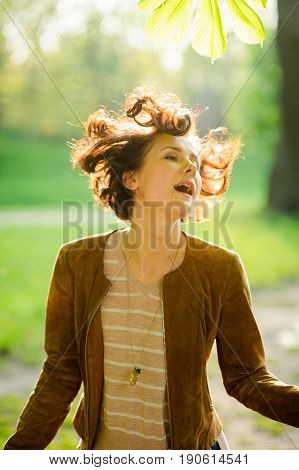 Portrait of the young cheerful woman in beams of the sun. Wind has disheveled a short brown hair. Against the background of the greenery of the spring park.
