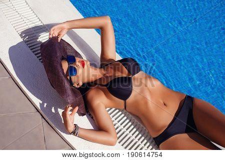 beautiful brunette young woman wearing black bikini, sunglasses and large hat sunbathing in swimming pool. outdoor fashion shot. copy space.