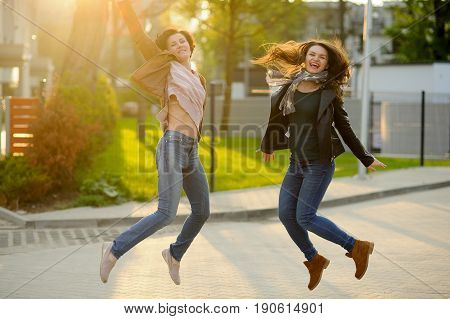 Two cheerful girlfriends. Girls as though soar above the ground. Serene spring day. Excellent mood.