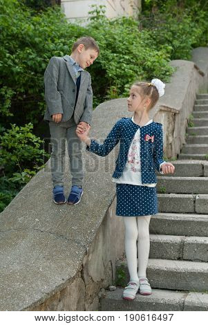 Little boy and older girl holding hands standing on concrete staircase in city and looking at each other smiling