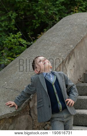 Funny little boy wearing a suit and a pullover looking up with a smile standing leaning against a concrete staircase in an alley