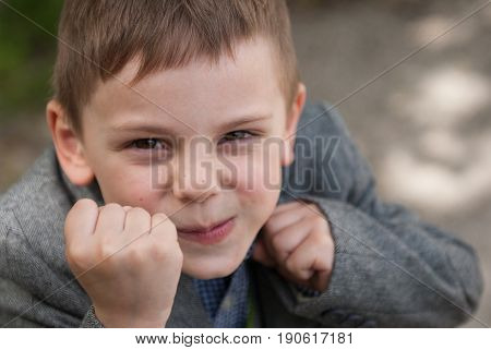 Little smiling boy threatens with fists taking boxing rack