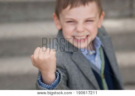 Little boy wearing jacket and sweater with grimace on his face threatens with his fist