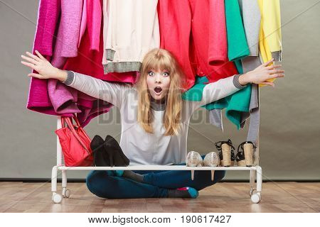 Suprised pretty woman sitting under clothing from wardrobe. Young undecided shopper girl bought new clothes. Shopaholic concept.
