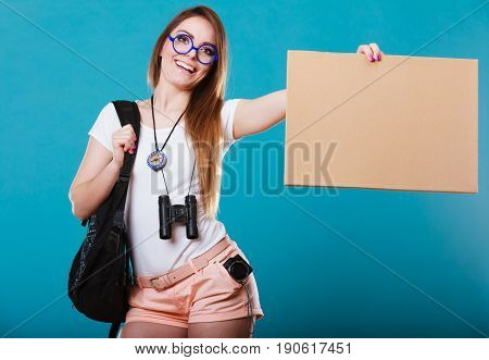 Travel and tourism active lifestyle concept. Woman tourist hitchhiking with blank sign for text on blue