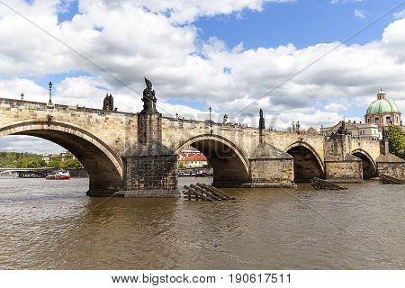 PRAGUE CZECH REPUBLIC - MAY 2 2017 : Charles Bridge on Vltava river in sunny day. Its construction started in 1357 under the auspices of King Charles IV. It is the most popular bridge in Prague there are always many tourists.