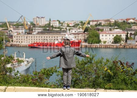 small boy in a jacket stands against the backdrop of a sea port placing his hands in the sides imitating a flight
