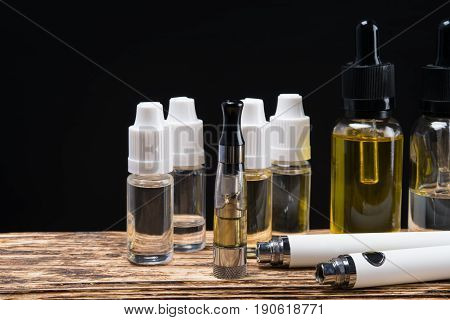 vaping set and liquid with aromas on a dark background