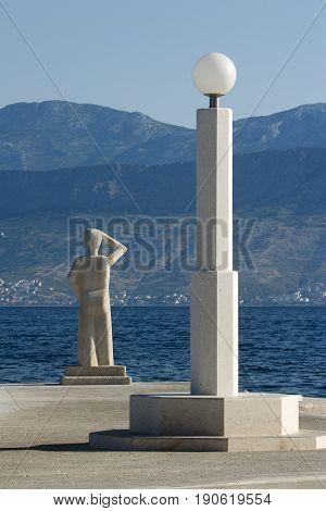 Postira on island Brac Croatia street lamp and monument to fishermans