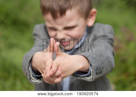 Little boy imitates a gun with his hands