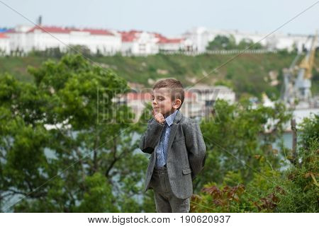Thinking little boy in a jacket against the backdrop of the sea trees and the old city holding his chin by hand