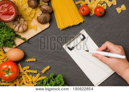 Italian Spaghetti Photo Recipe. Hand With Pen Writting On Blank Paper On The Kitchen Table Surrounde