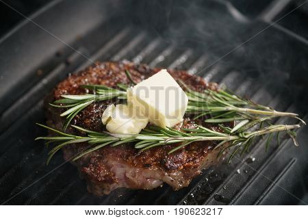 beef rib eye steak with rosemary on grill pan closeup, shallow focus
