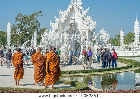 CHIANG RAI, THAILAND - FEBRUARY 4, 2016:Buddhist monks at famous ornate Wat Rong Khun (White Temple) in Chiang Rai northern Thailand. Thus unconventional Buddhist temple is an ongoing project.