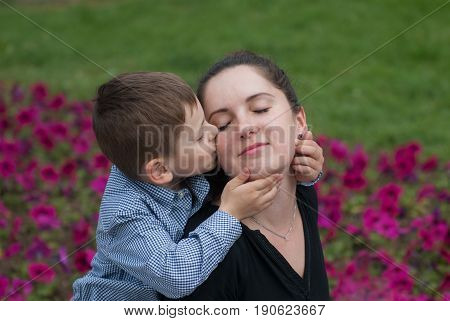 happy little boy gently kisses his mother who closed her eyes with pleasure