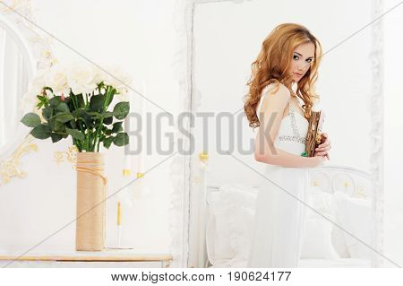 Beautiful girl with brown long hair stands near a mirror holding an album with photos in her hands - Portrait of a young woman in a white room, a boudoir, in a white dress