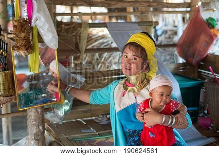 CHIANG RAI, THAILAND - FEBRUARY 4, 2016: Karen long neck woman with small kid in a village between Chiang Rai and Chiang Mai. Karen is one of several ethnic hill tribes in northern Thailand.