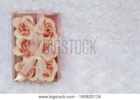 Beautiful roses candles and gift box on a white background. Soft fluffy white veil