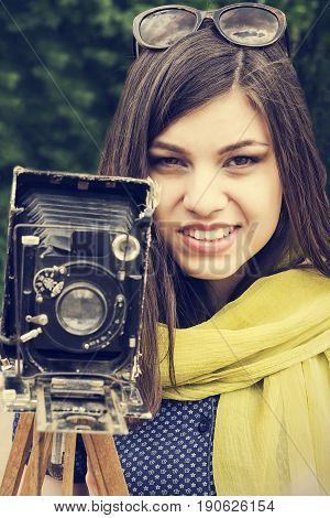 Portrait of a beautiful young girl with a retro camera. Retro style.