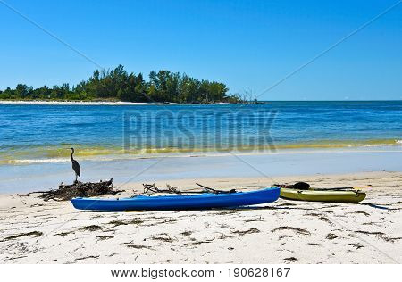 Colorful plastic Kayaks on a white sandy beach