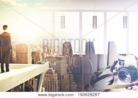 Back view of businessman standing on rooftop. Abstract city background with sunlight camera and meeting room. Double exposure