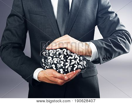 Businessman holding pile of drawn question marks on grey background. FAQ concept