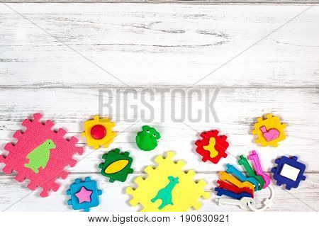 Various baby toys frame, white wooden background, copy space