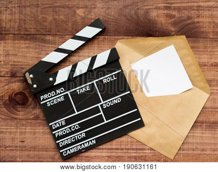 Vintage Classic Clapperboard And Envelope On Brown Wooden Table