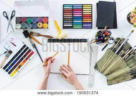 Artist drawing graphic sketch at sketchbook. Workplace, workspace. Top view photo of artistic tools lying on work-table: gouache, crayons palette and paintbrush collection