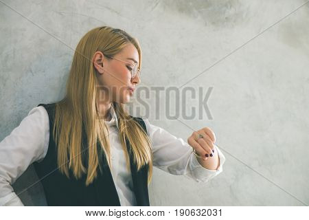 Business and time management concept. Young businesswoman looking at wrist watch. Time is money