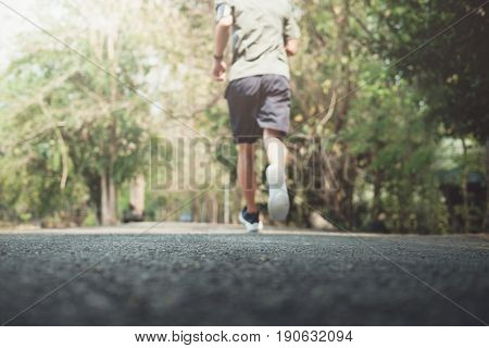 Blurred Man Is Jogging In The Morning. Young Man Doing Sports And Jogging In A Park.