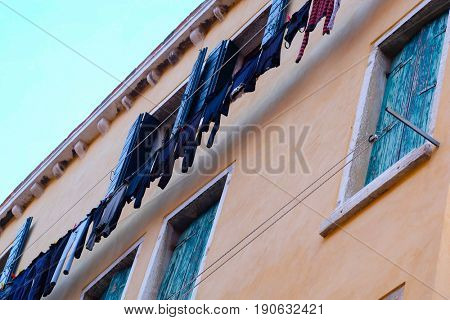 Venice, Italy, May, 31, 2017: facade of an inhabitable house with drying linen at sunset in Venice, Italy