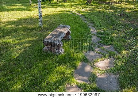 Old handmade wooden bench standing on lawn near white birch in the park or garden close to the left turn of sandstone footpath.