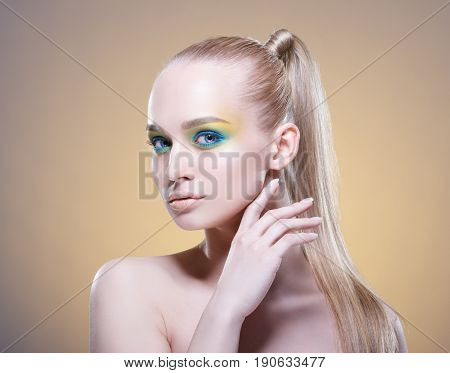 Beautiful woman with bright makeup and long blond hair.