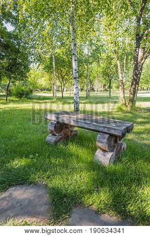 Old handmade wooden bench standing on lawn near white birch in the park or garden from the right of sandstone footpath.