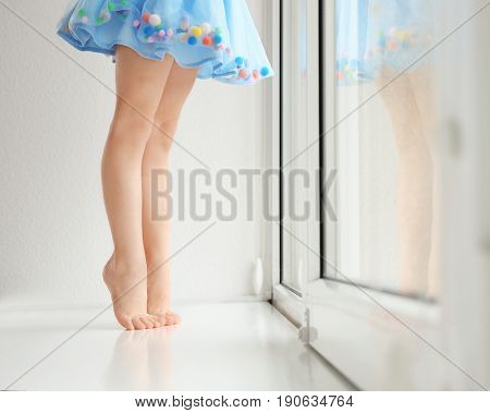 Legs of little girl standing on windowsill