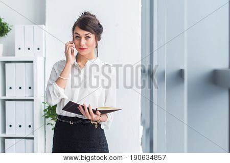 Attractive female employee speaking on the phone, having negotiations, using mobile phone and tablet in office