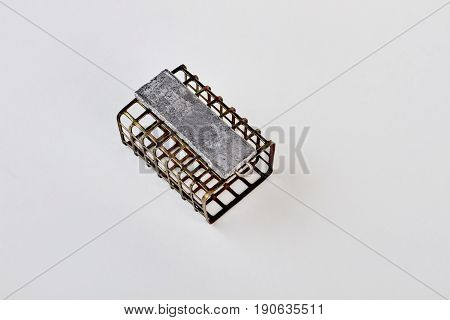 Metal fishing feeder, top view. Steel feeder, cargo, white background. Accessories for fishermen.