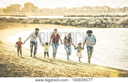 Happy multiracial families running together at beach holding hands on vacation - Multicultural summer joy concept with mixed race people having fun outdoor at sunset - Warm vintage backlight filter